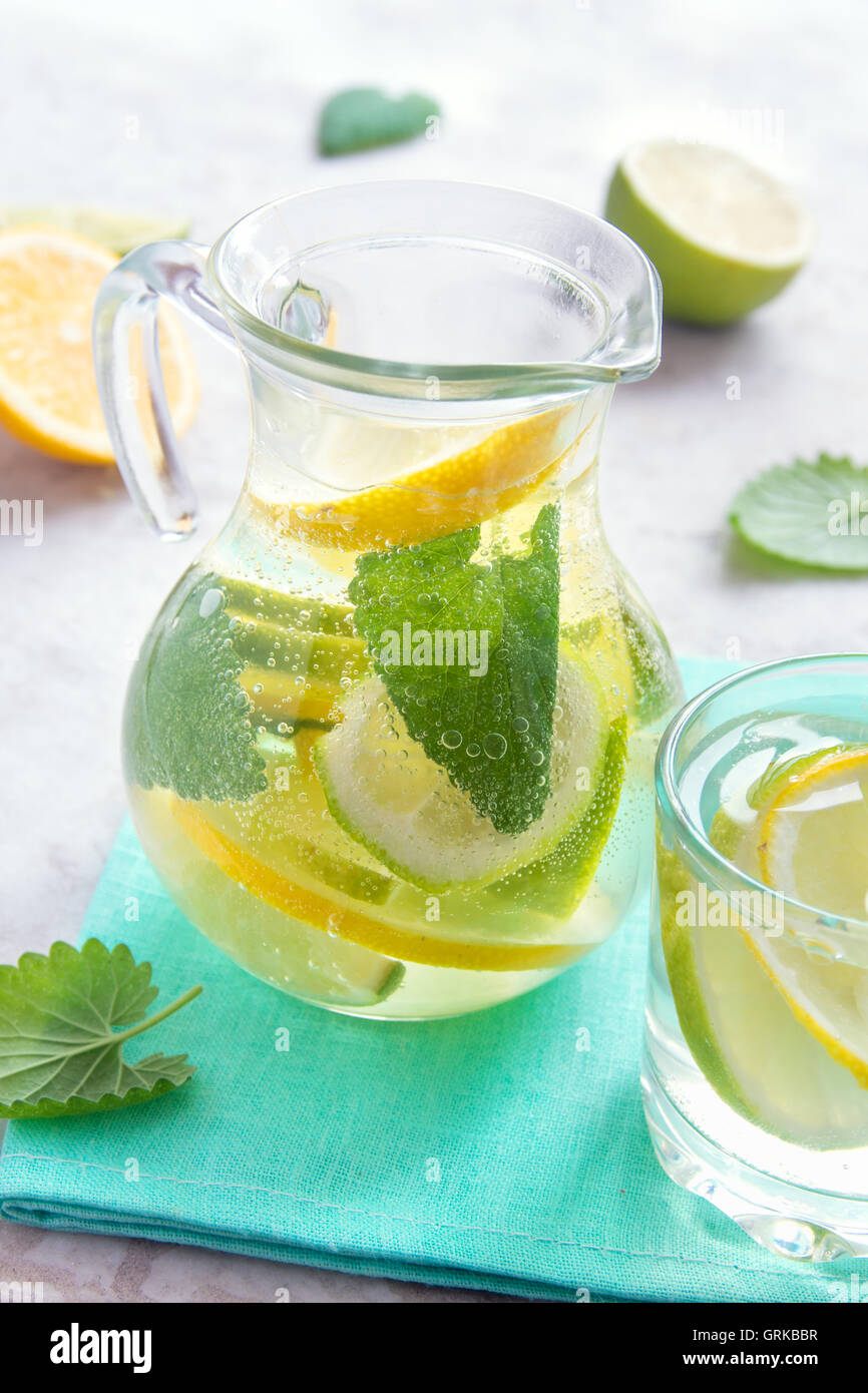Detox water (lemonade) with lime, lemon and mint in glass jug - Stock Image