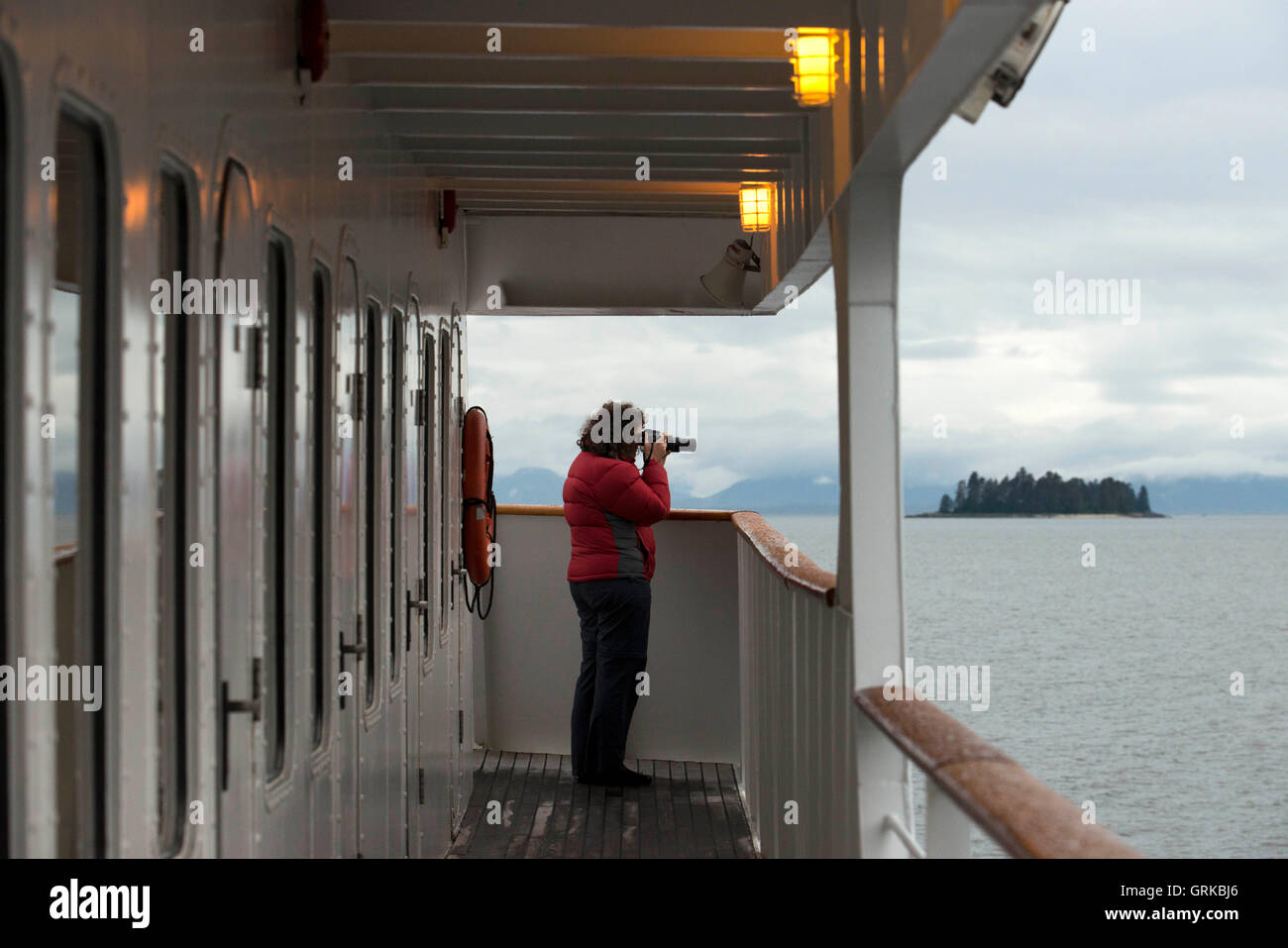 Woman doing photos in Safari Endeavour cruise at Five Fingers Lighthouse. Frederick Sound. Stephen's Passage. - Stock Image
