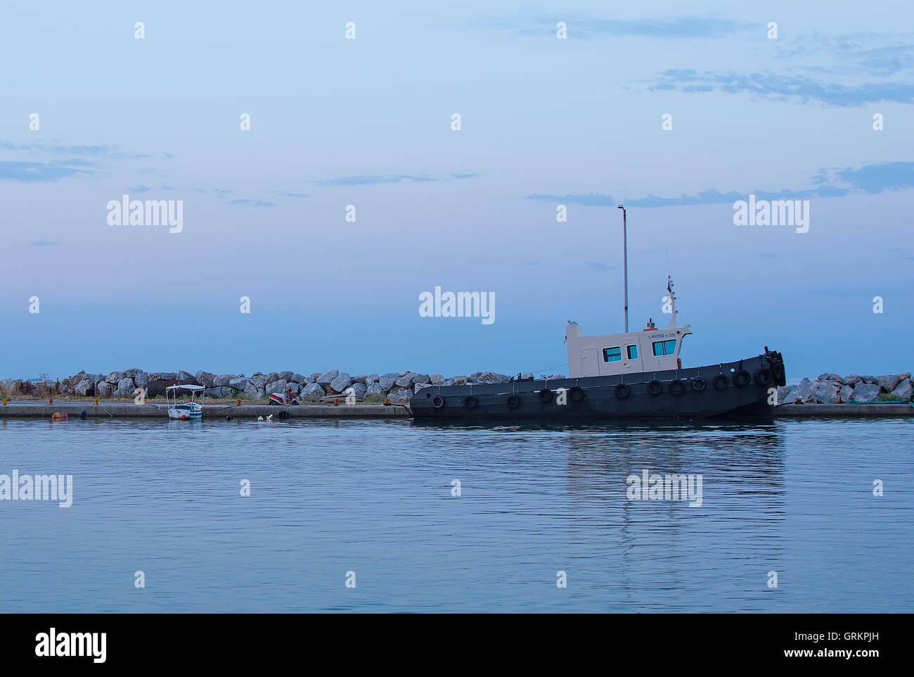 Towboat in the Harbor at Sunrise. Docked Tugboat in the Port at Dawn. Ship in the Sea Bay. - Stock Image