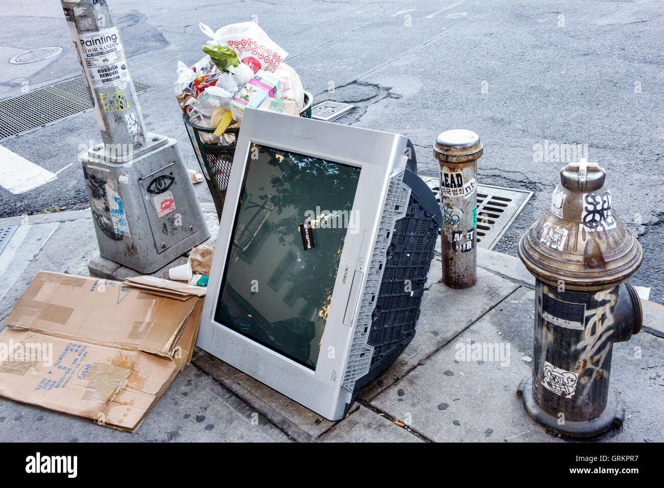 Lower Manhattan New York City NYC NY street corner trash garbage waste illegal dumping television set environment - Stock Image