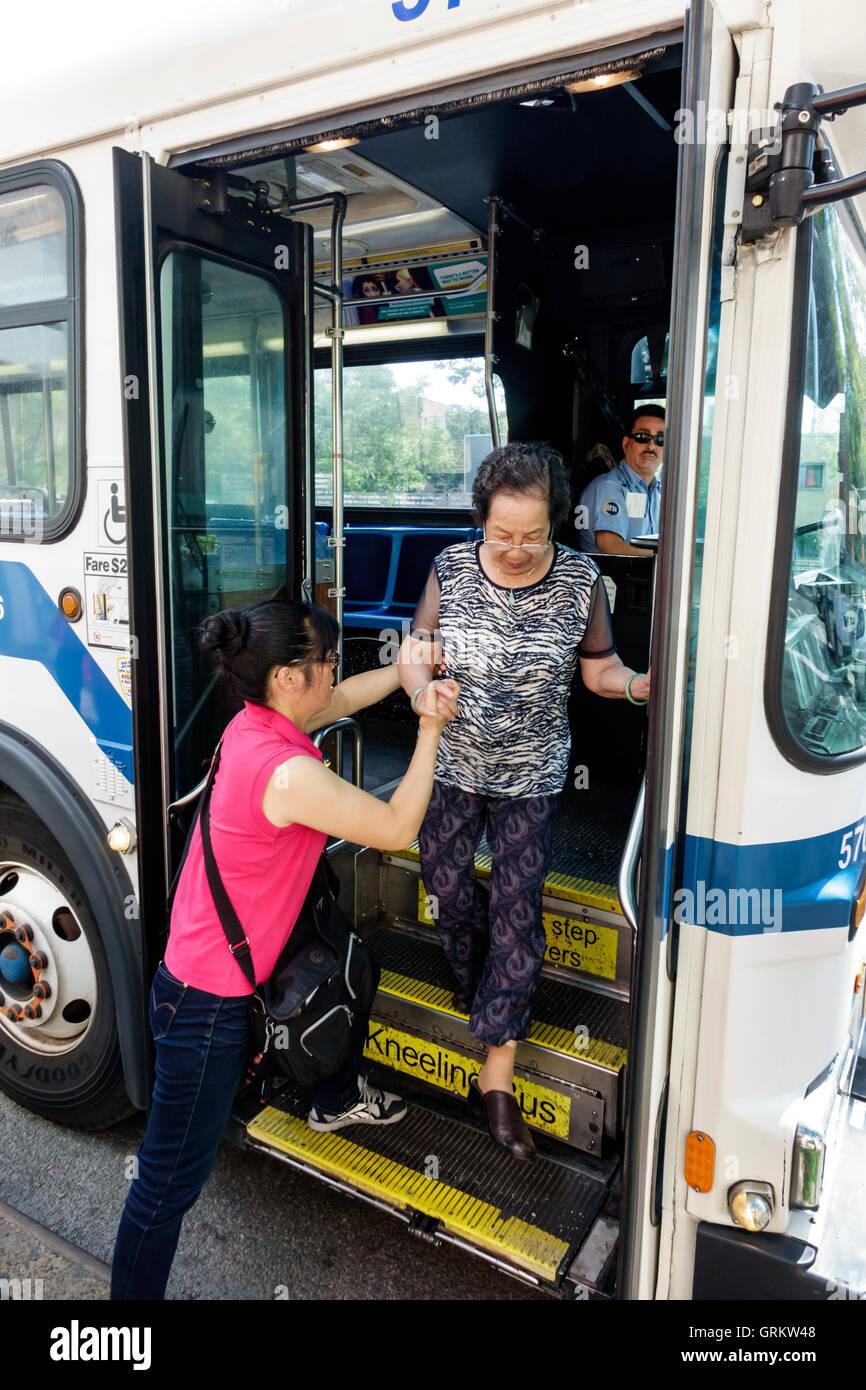 Lower Manhattan New York City NYC NY Chinatown MTA public transportation bus stop Asian woman man elderly exiting - Stock Image