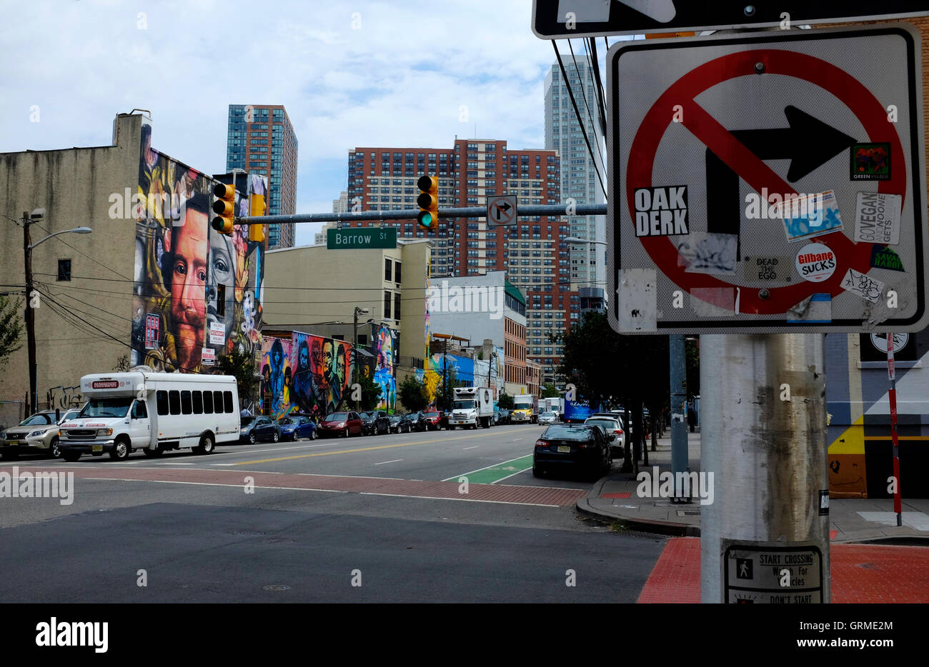 Graffiti and murals on traffic signs and building facade along Christopher Columbus Drive in Jersey City,New Jersey,USA - Stock Image