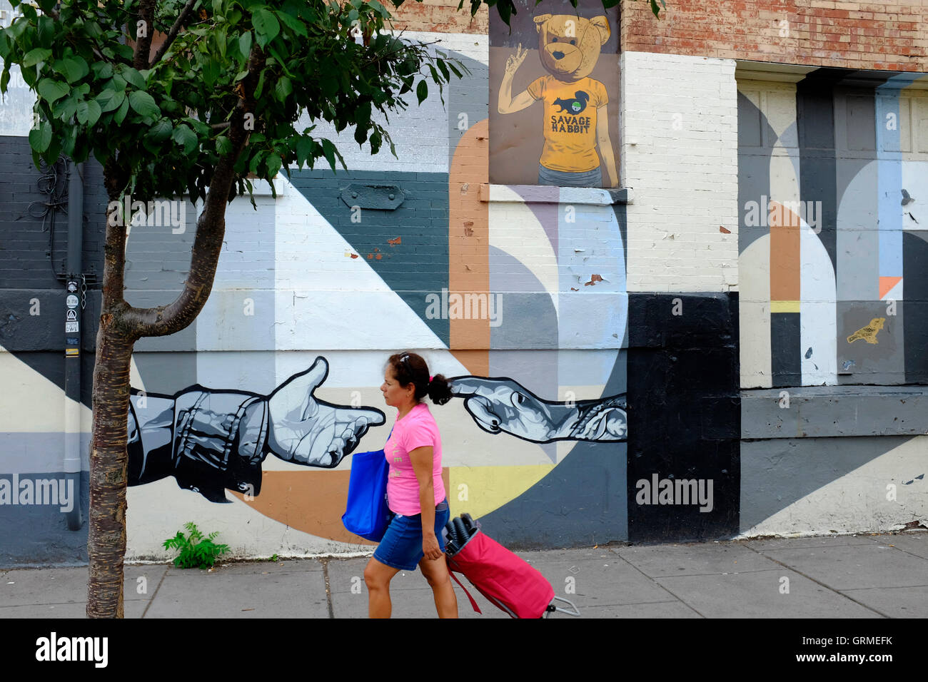 A woman walking by a mural along Christopher Columbus Drive in Historic Downtown,Jersey City,New Jersey,USA - Stock Image