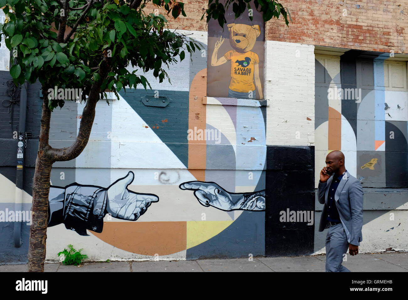 A man walking by a mural on the building facade along Christopher Columbus Drive in Historic Downtown,Jersey City,New - Stock Image