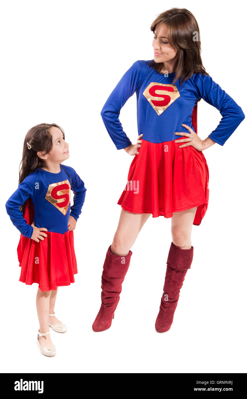 Mother and young daughter happily interacting together, both dressed in superman outfits with red skirts, all white - Stock Image