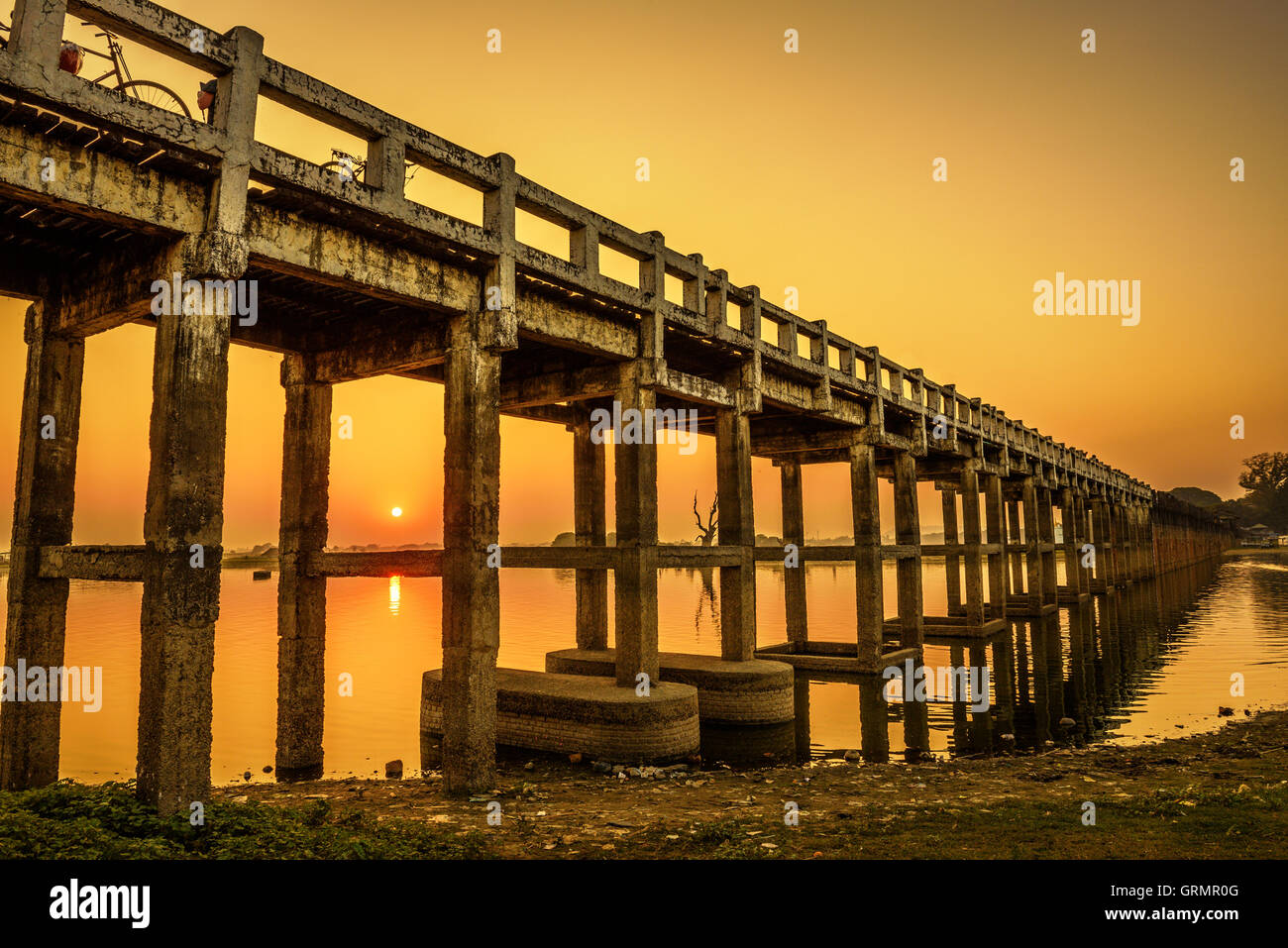 Sunset over the historic wooden U Bein Bridge near Mandalay in Myanmar. Long exposure. - Stock Image