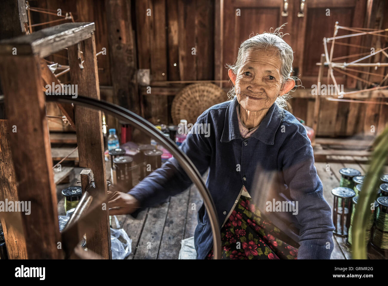 Woman worker weaves fabric in a weaving factory on Inle Lake - Stock Image