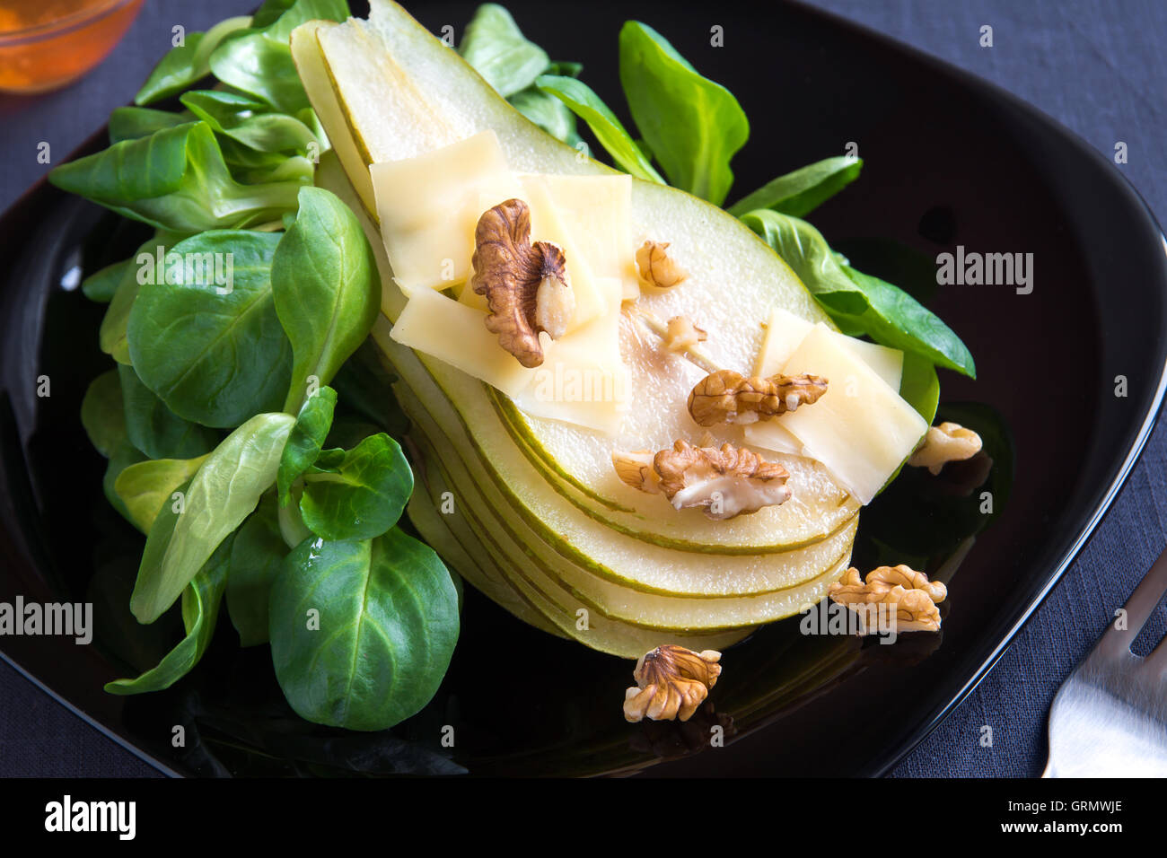 Pear salad with parmesan cheese and walnuts Stock Photo
