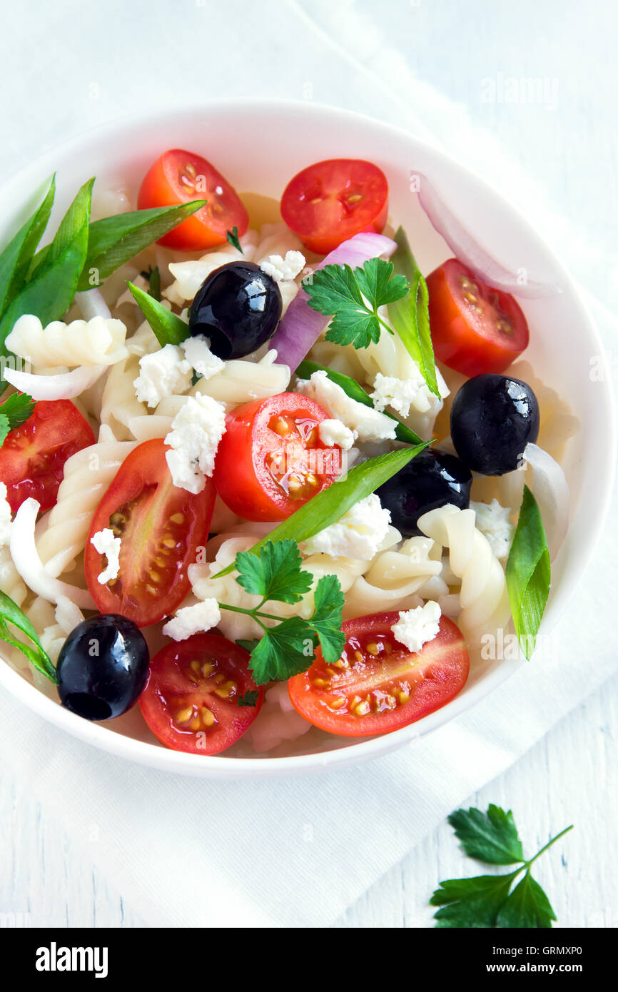 Pasta salad with vegetables, olives and feta over white background - Stock Image