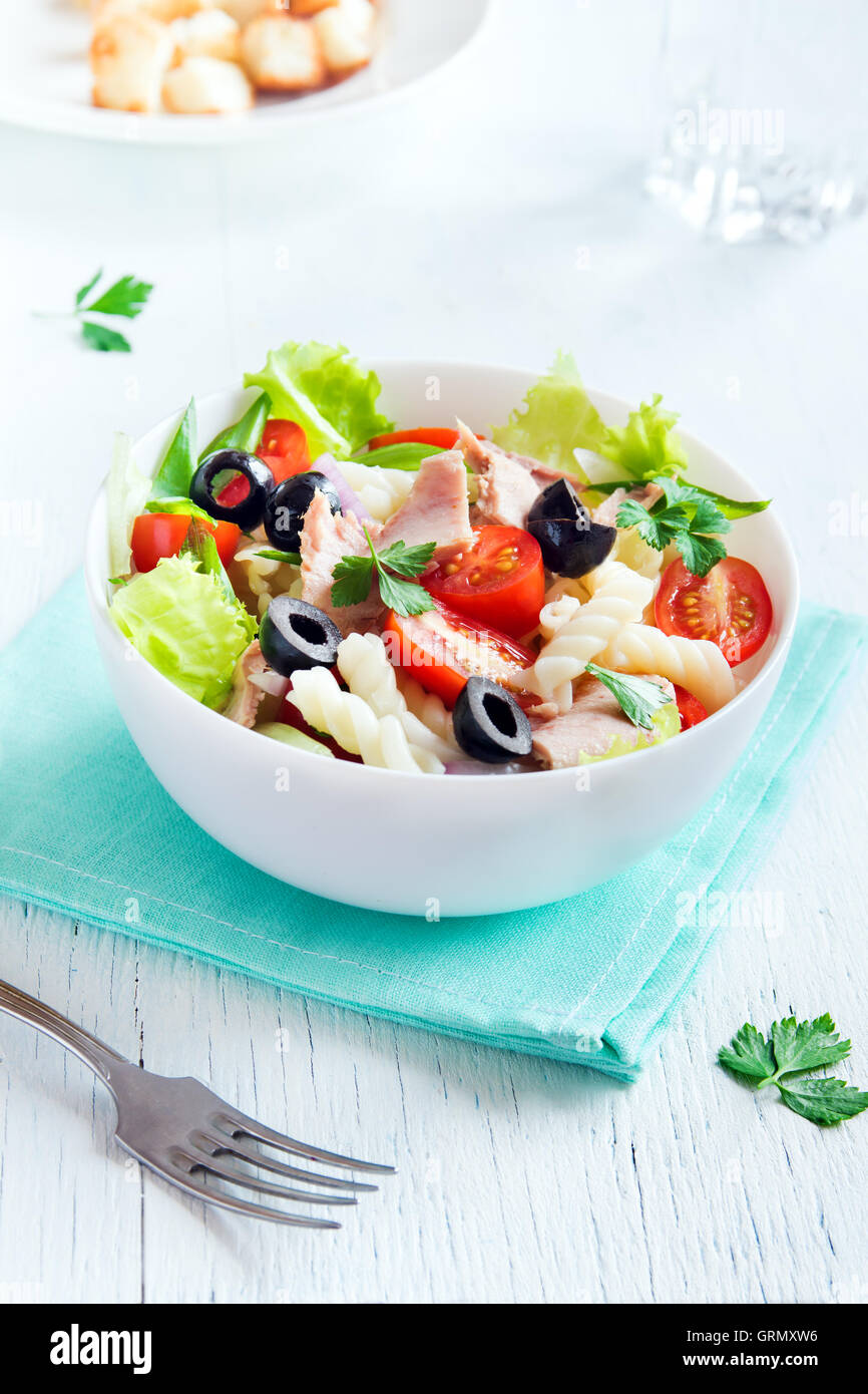 Tuna and pasta salad with fresh tomatoes, olives, herbs in bowl over white wooden background - Stock Image