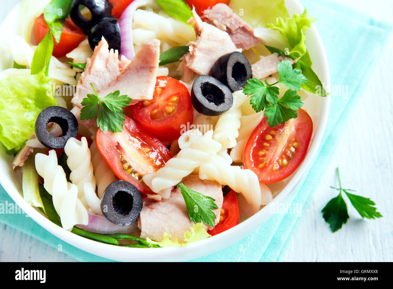 Tuna and pasta salad with fresh tomatoes, olives, herbs close up - Stock Image