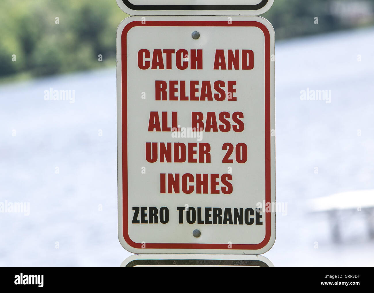 A 'Catch and release all bass under twenty inches' sign. - Stock Image