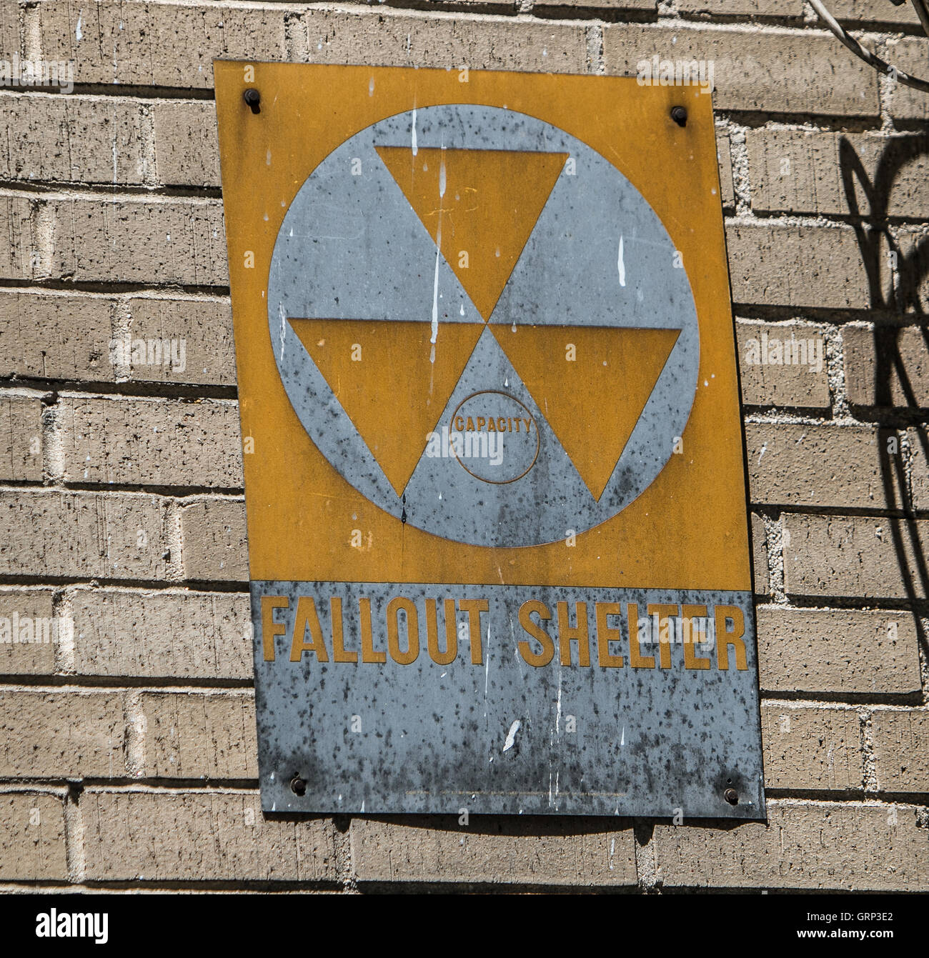 "A ""Fallout Shelter"" sign on a brick building wall. Stock Photo"