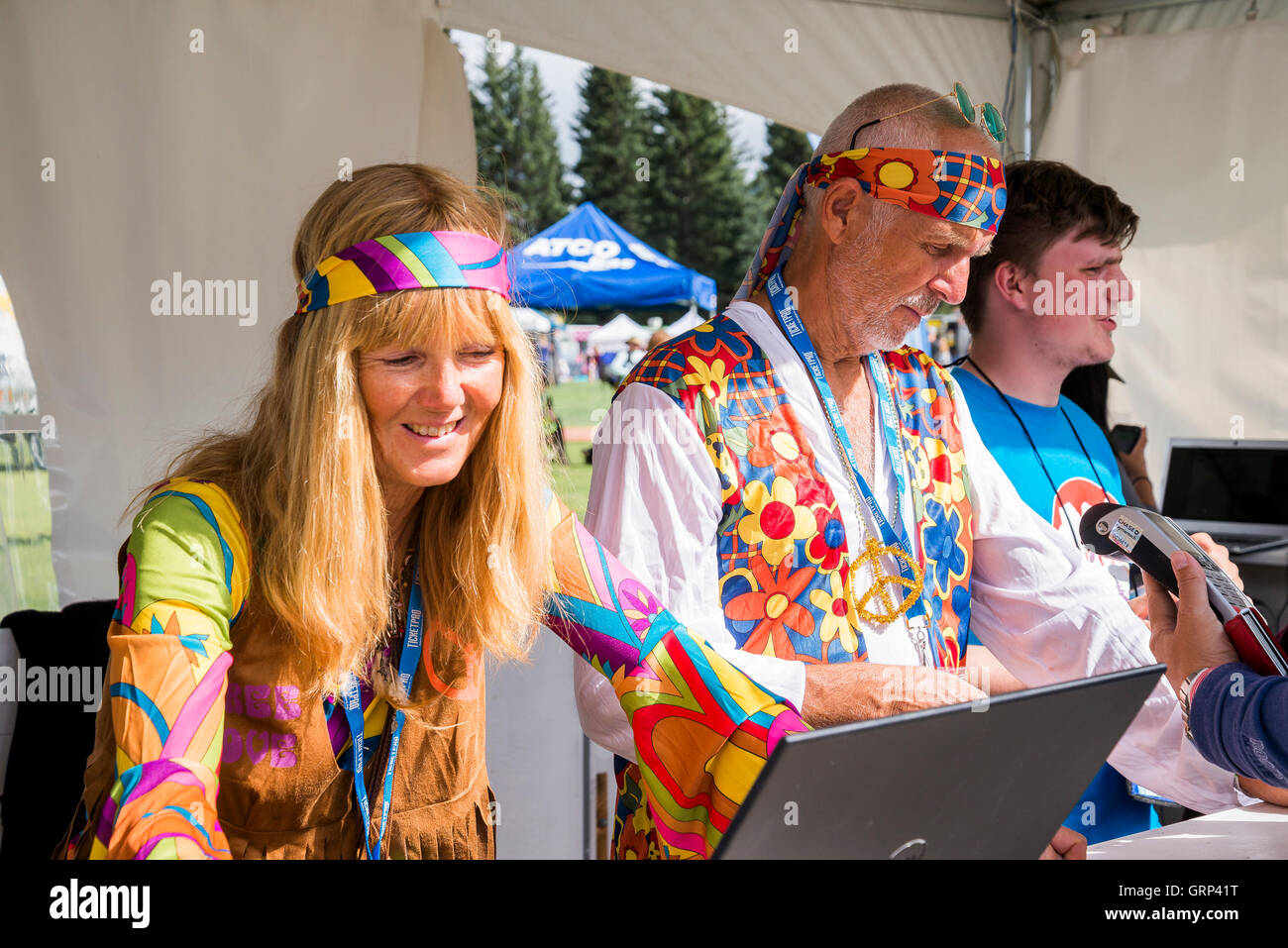 Music event ticket sellers dressed as hippies. - Stock Image