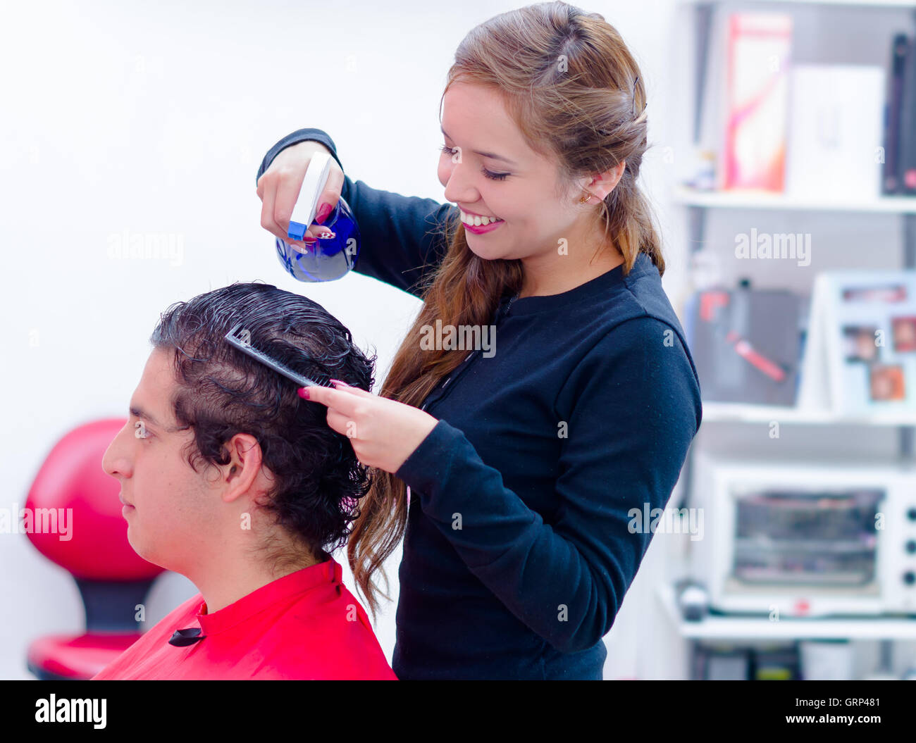 Spontaneus and smiling hairstylist is getting wet her next client, comb and spray on her hands Stock Photo
