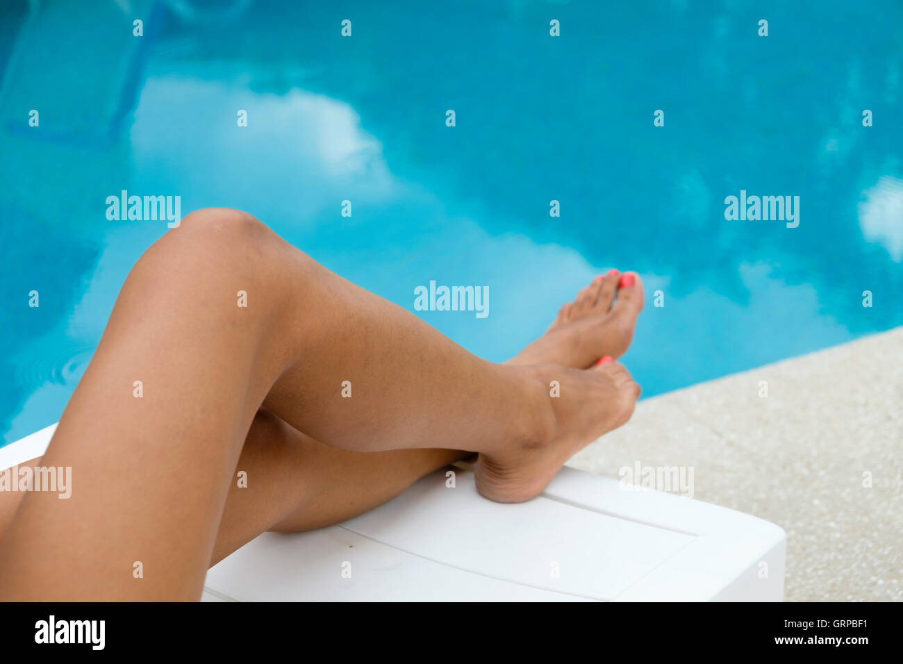 Groovy Attractive Legs Of Young Woman On A Pool Side Lounge Chair Ncnpc Chair Design For Home Ncnpcorg