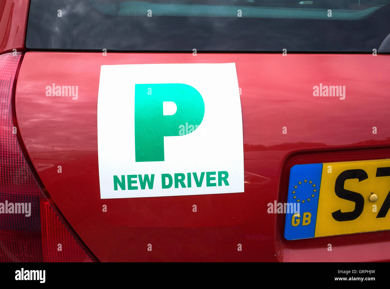 A green UK new driver plate on a red car - Stock Image