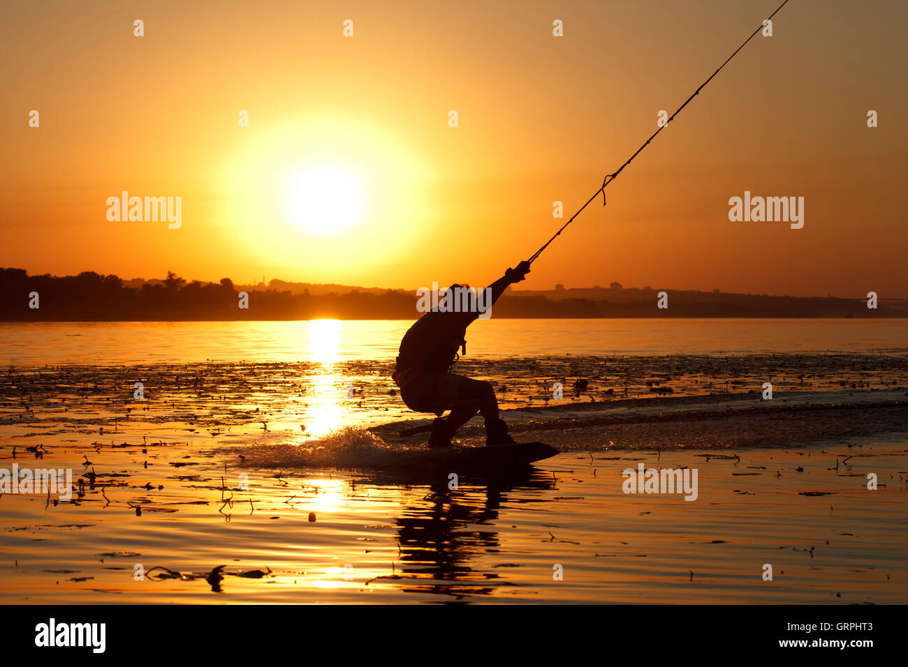 a wakeboard, athlete silhouette on sunset background - Stock Image