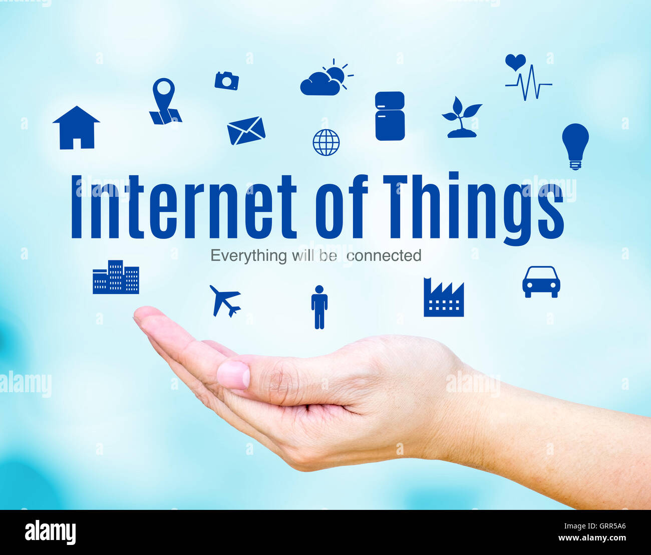 Open hand with Internet of Things (IoT) word and icon on blue blur background, Technology concept. - Stock Image