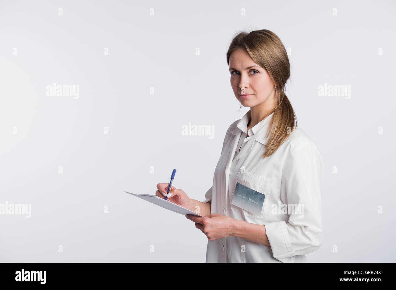 Cheerful medical doctor woman taking notes. Isolated on white Stock Photo