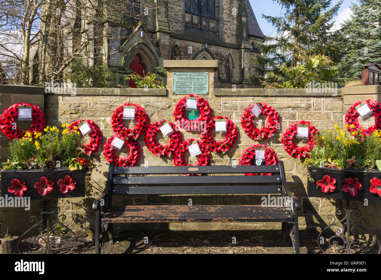 Greenmount Village war memorial with many poppy wreaths, the village remembrance of the twelve men of Greenmount, - Stock Image