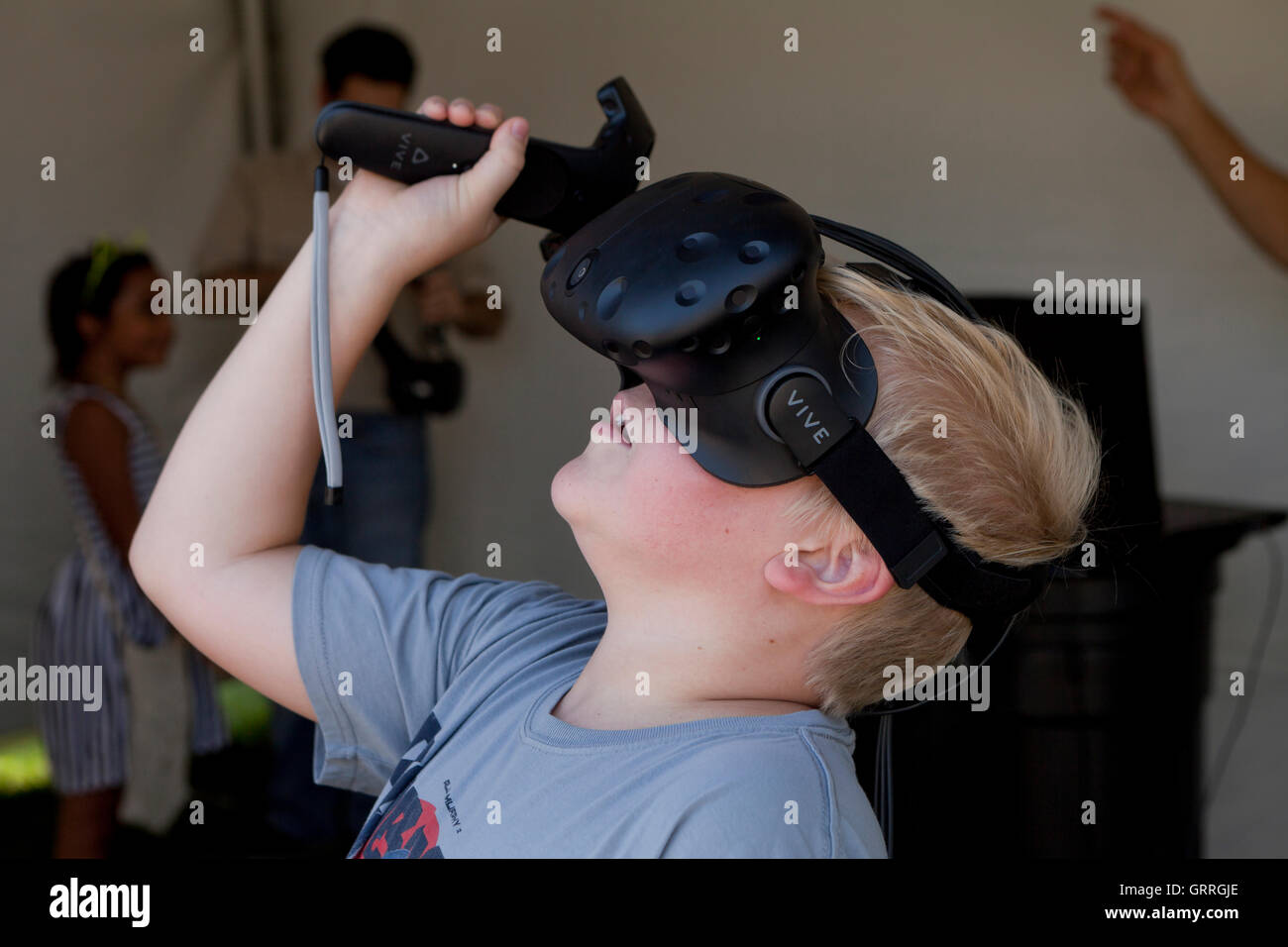 Child wearing VR headset (VR goggles) using bluetooth controller - USA - Stock Image