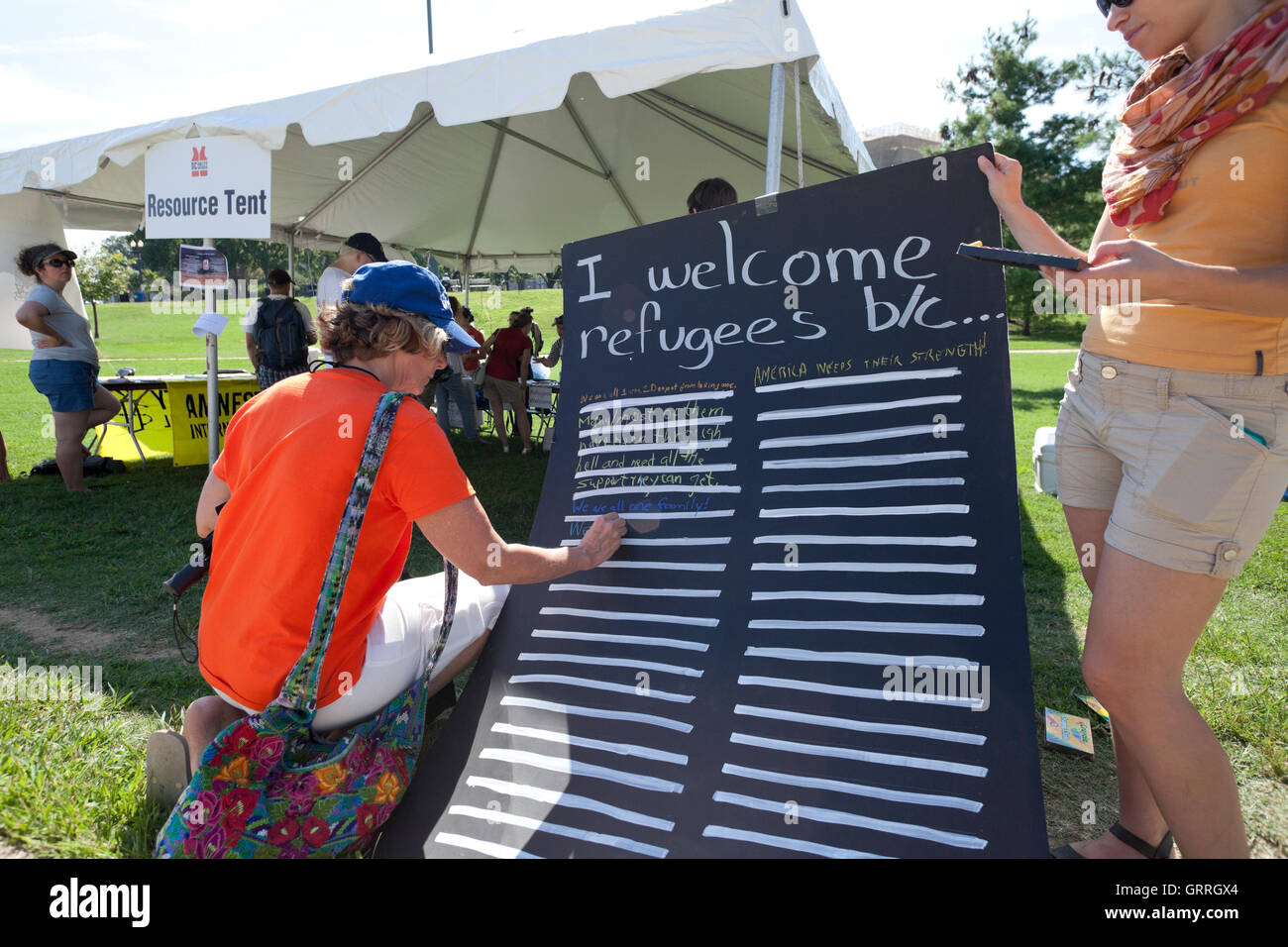 Pro-refugee activist holding sign - Washington, DC USA - Stock Image