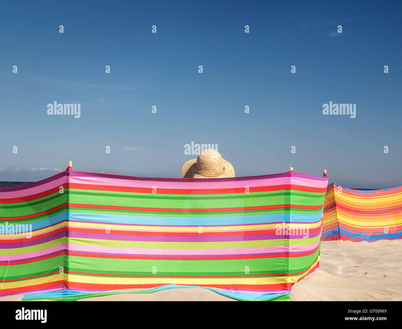 Female sunbather in straw hat relaxing on the beach behind windbreak - Stock Image