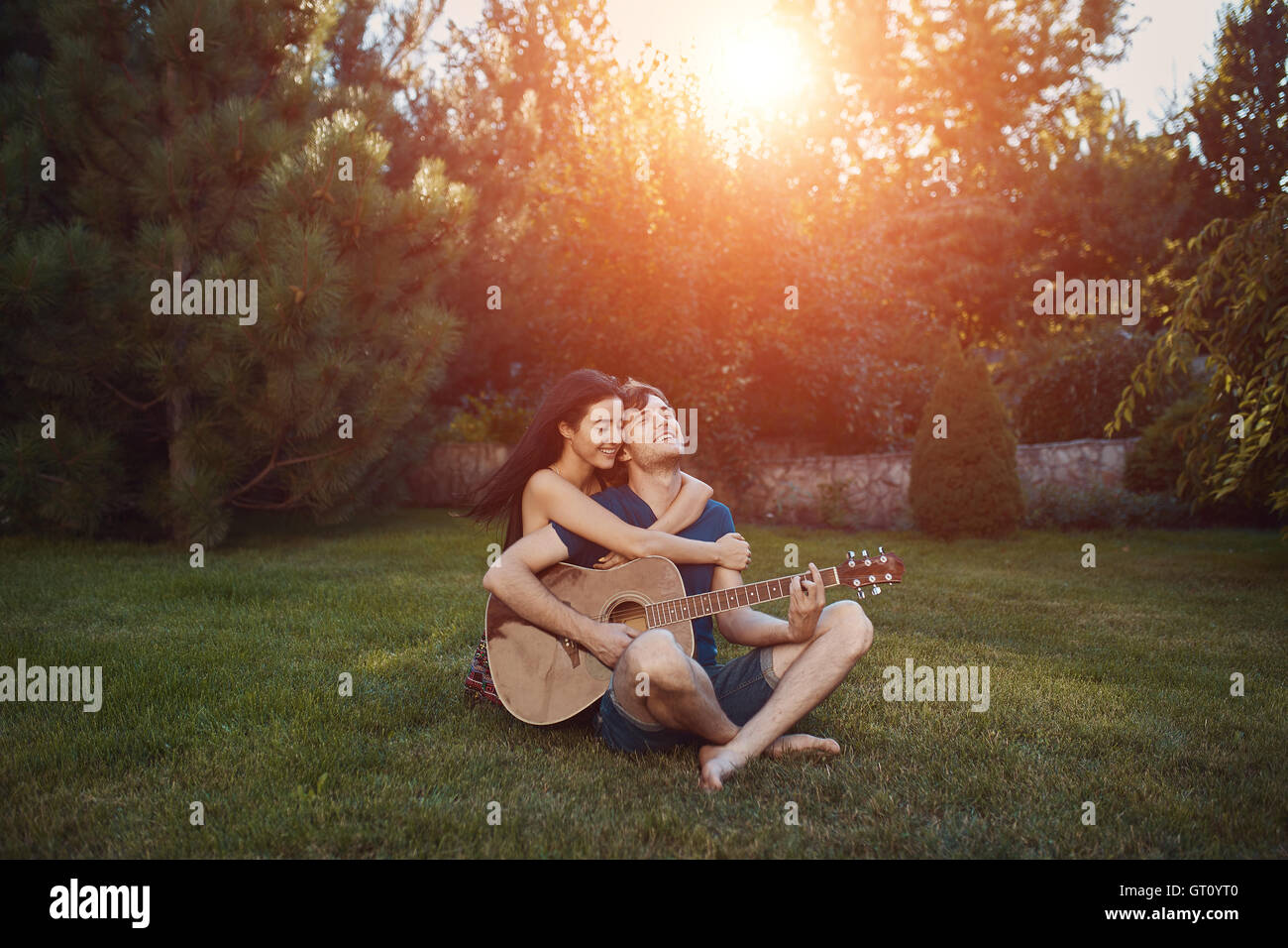 Handsome romantic couple sitting on the grass in the garden - Stock Image
