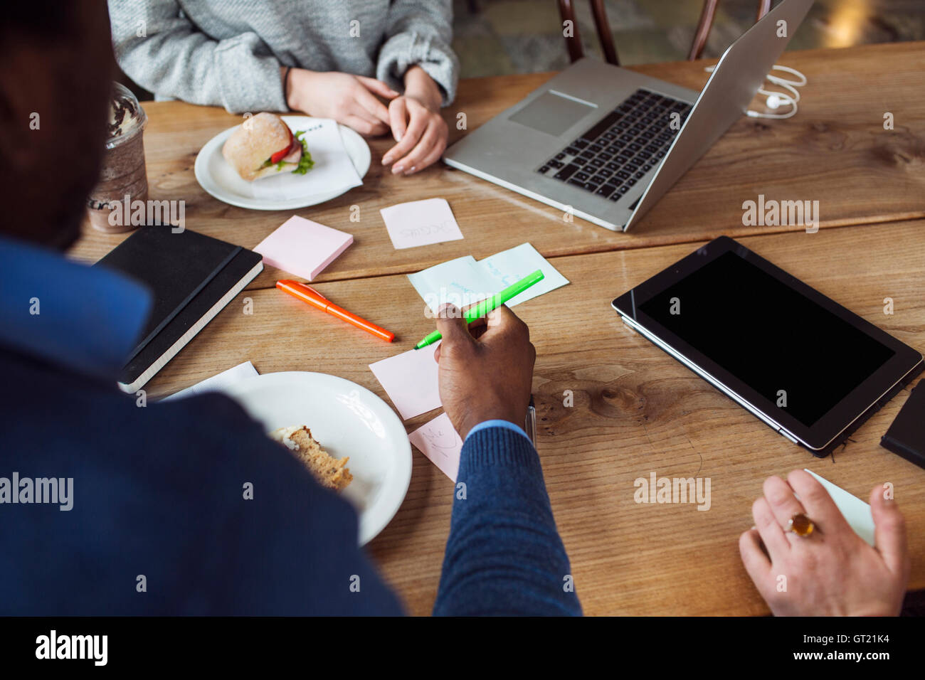 Cropped image of friends working while having sandwich at cafe - Stock Image
