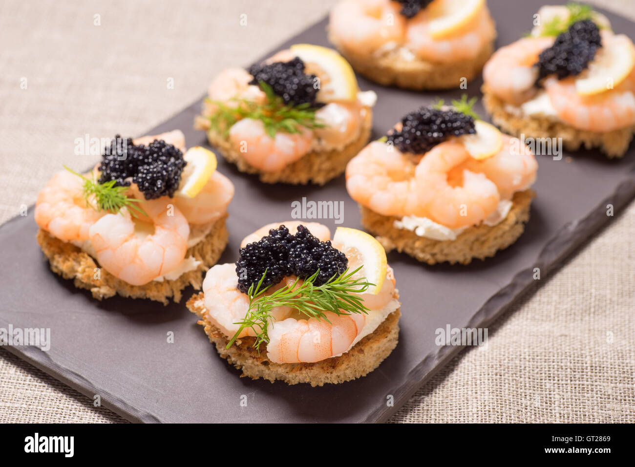 Shrimp Appetizer served on toasted bread and served on a slate plate - Stock Image