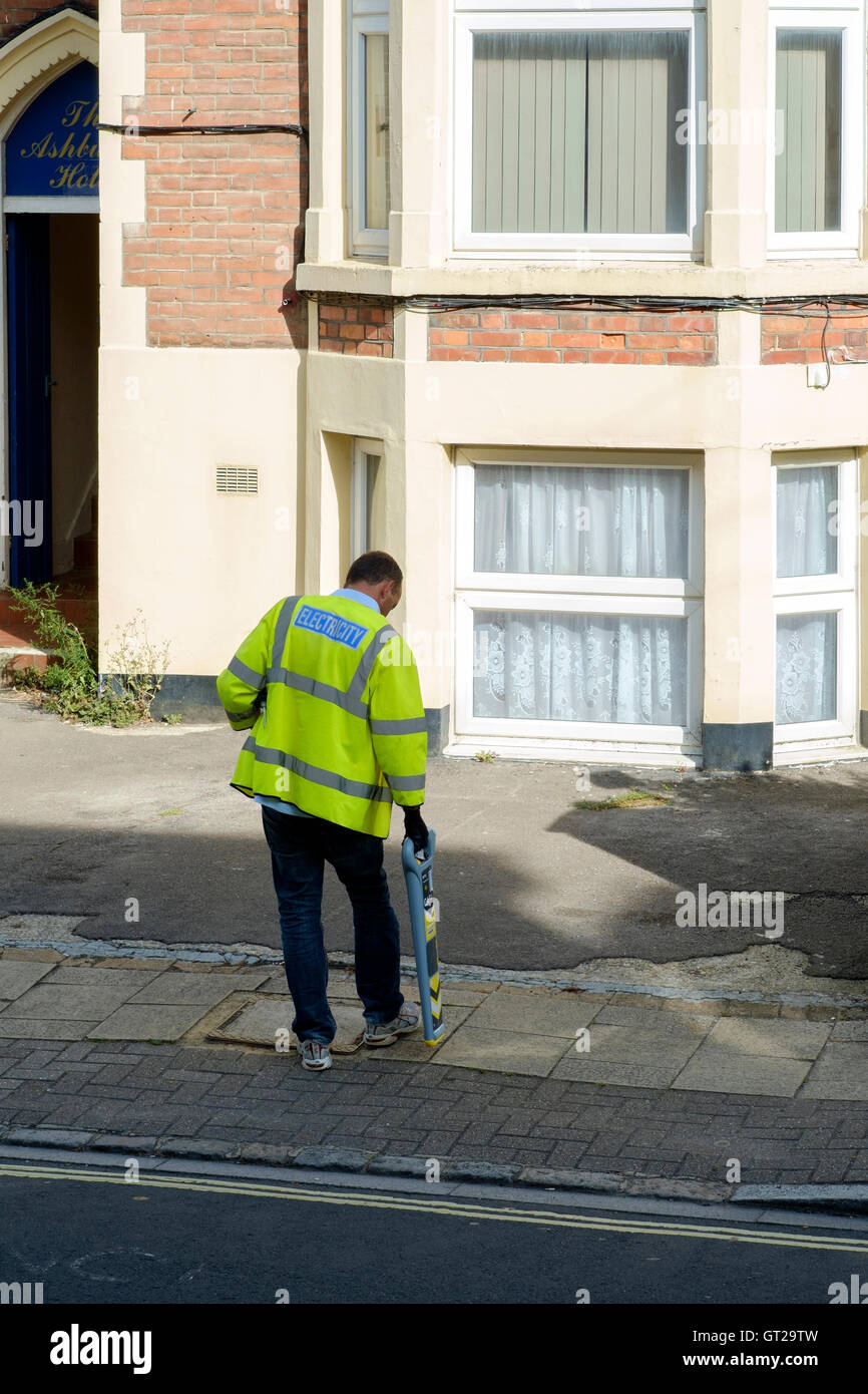 male electricity worker using a metal detector on the pavement to detect cables england uk - Stock Image