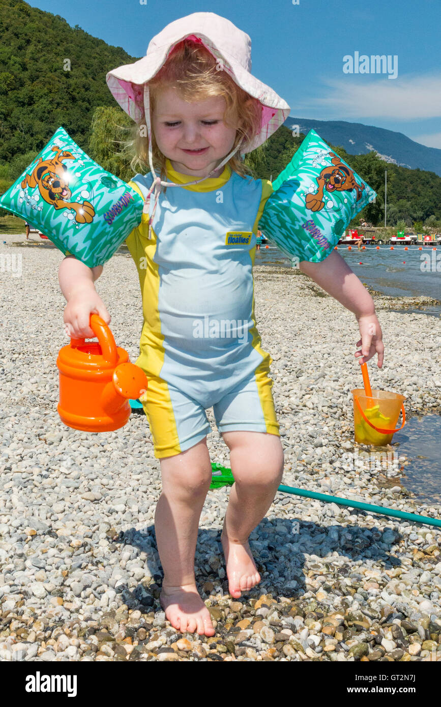 Two 2 year old girl toddler child / kid with sun hat, swim suit bathing costume, factor 50 sun cream to protect - Stock Image
