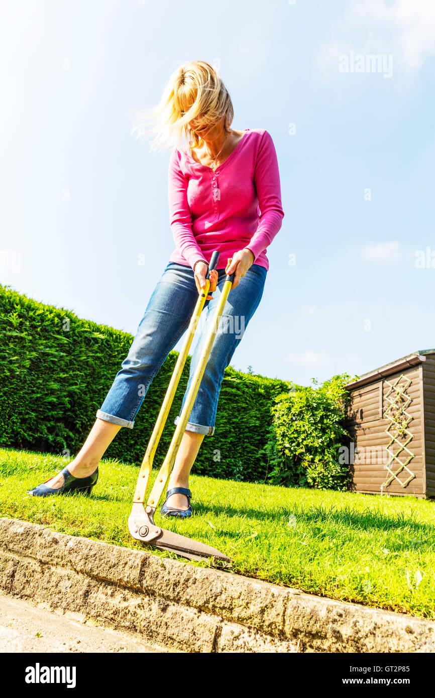 Cutting grass with long handled shears edging shears trimming edge woman gardening gardener hedge cutting UK England - Stock Image