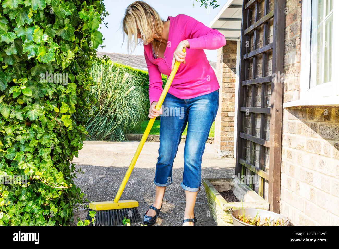 sweeping up mess broom brushing sweep gardening gardener hedge cuttings UK England GB clearing - Stock Image