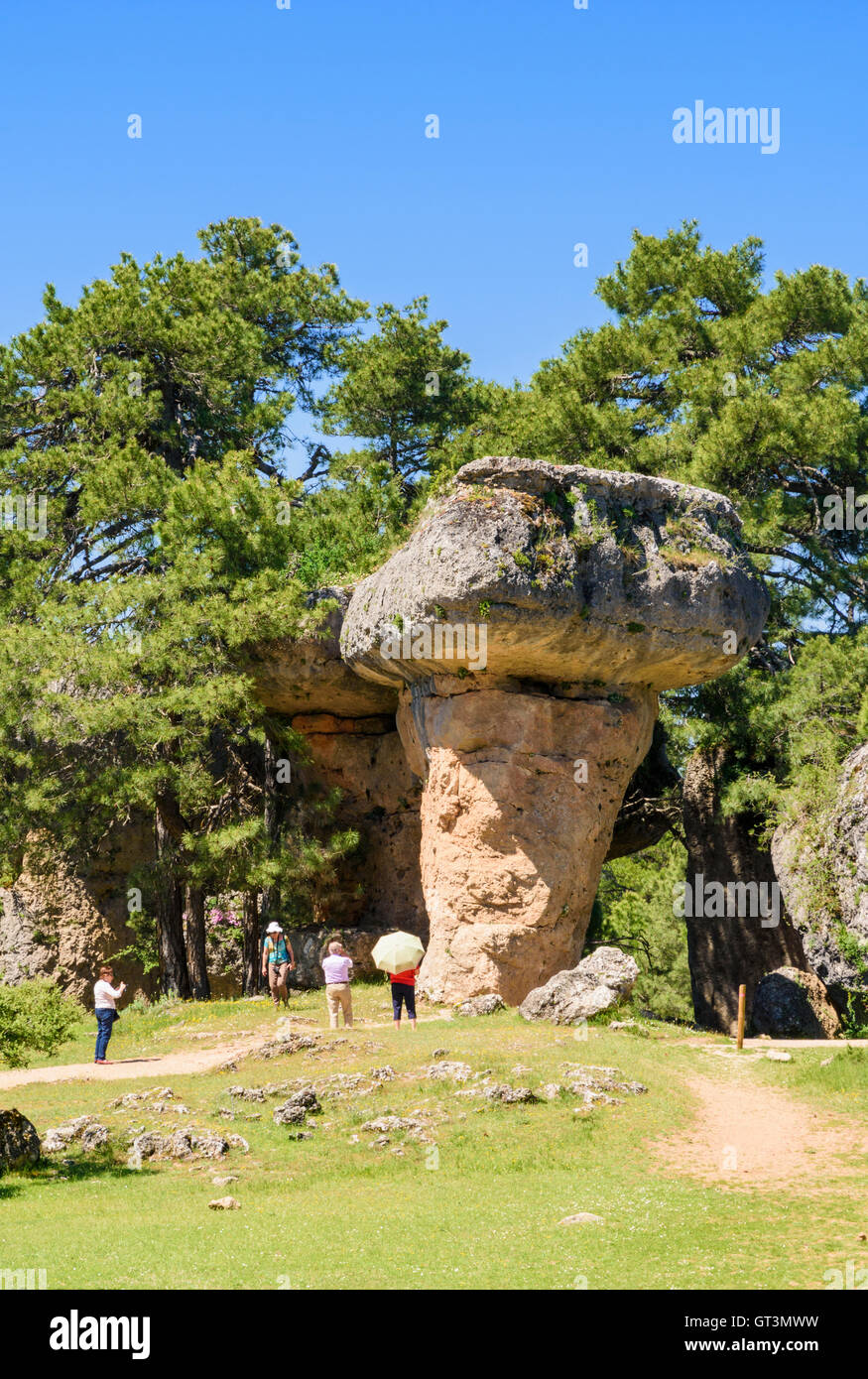 Tourists exploring rock formations shaped by erosion in La Ciudad Encantada near Cuenca, Spain - Stock Image