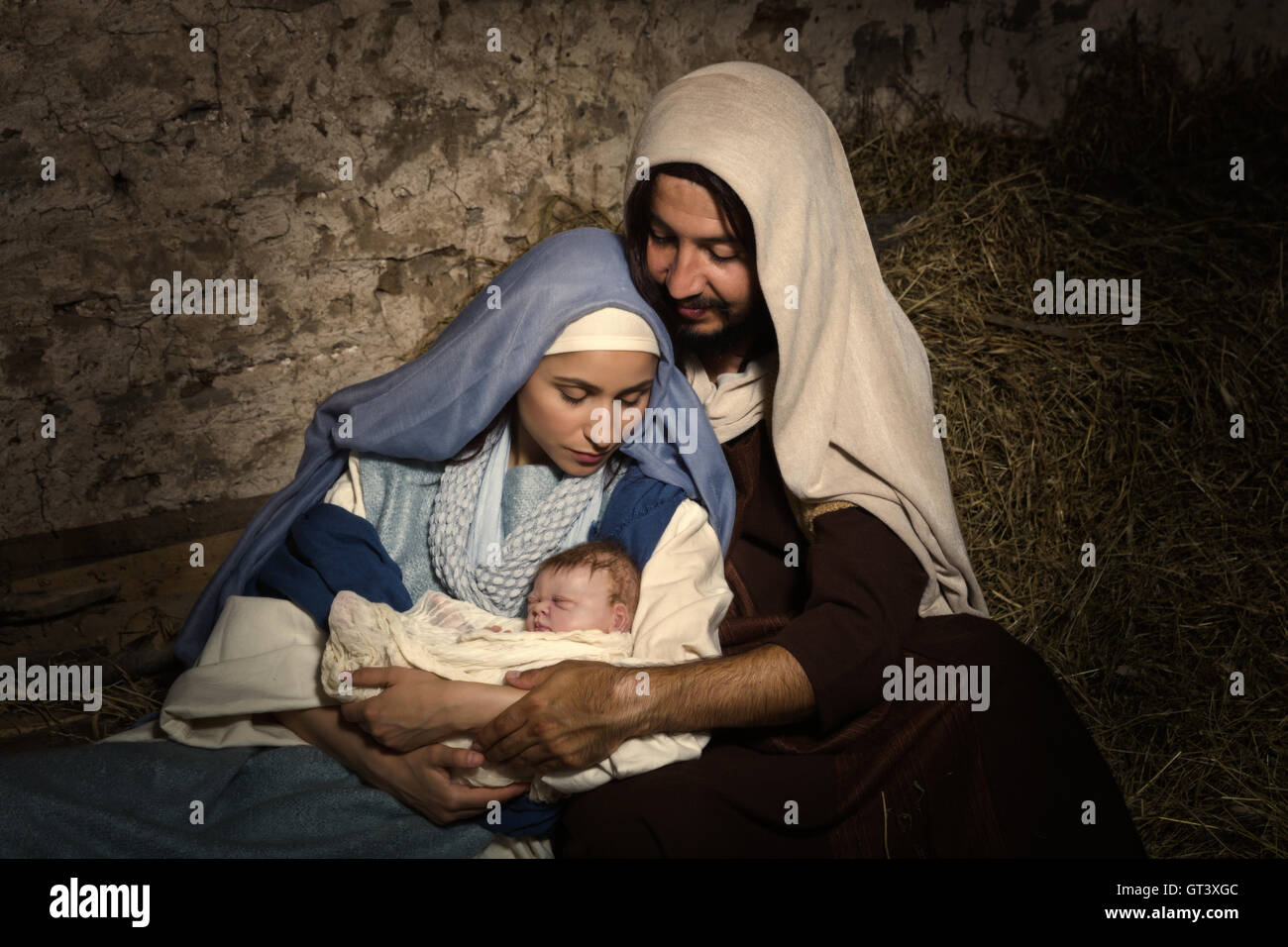 Live Christmas nativity scene in an old barn - Reenactment play with authentic costumes.  The baby is a (property - Stock Image