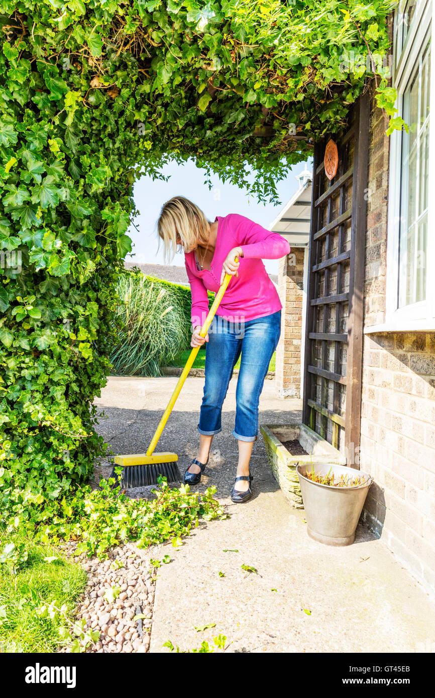 sweeping up mess broom brushing sweep gardening gardener hedge cuttings UK England GB Stock Photo