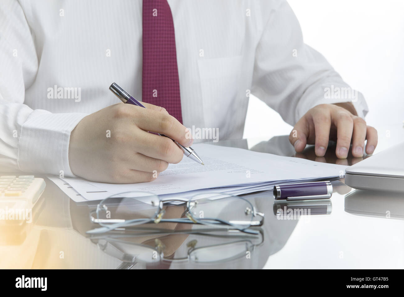 Businessman working with documents on office desk with calculator, laptop computer and glasses. - Stock Image