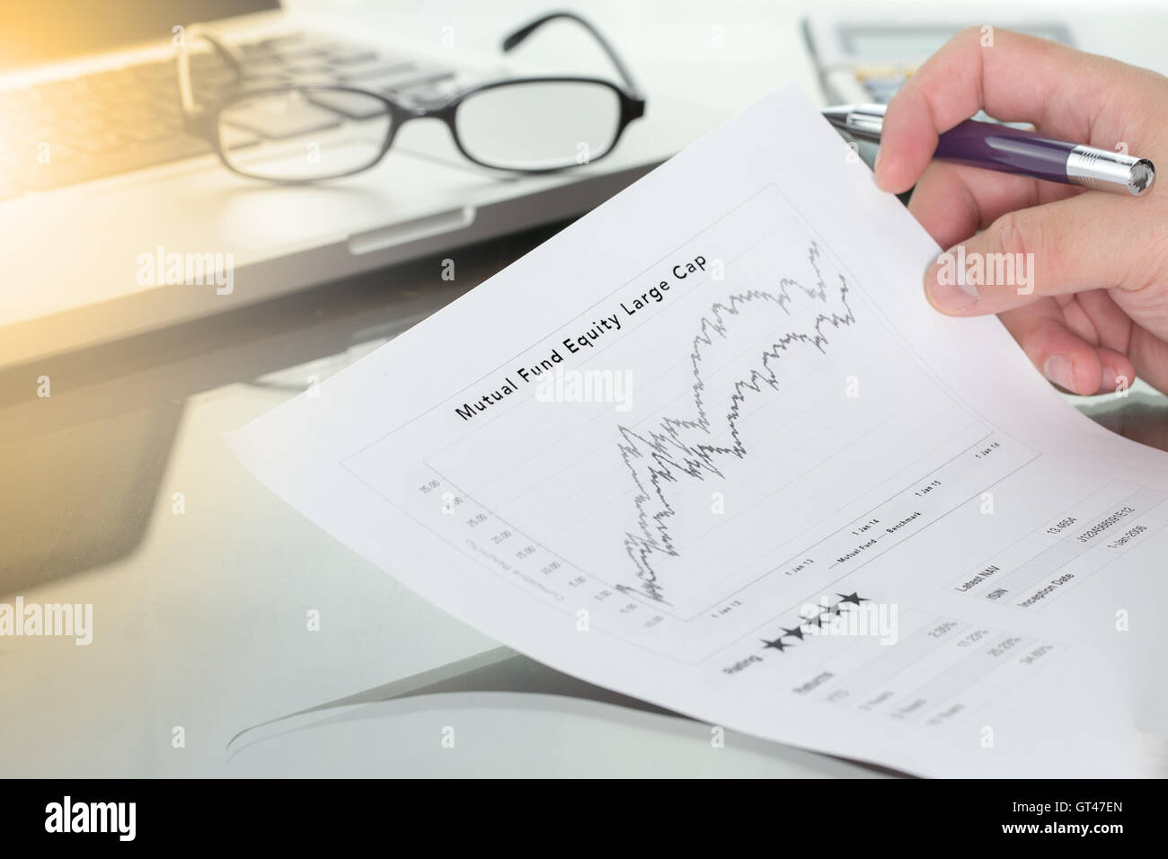 Businessman or fund manager review Mutual Fund information with performance line graph and benchmark with pen calculator - Stock Image