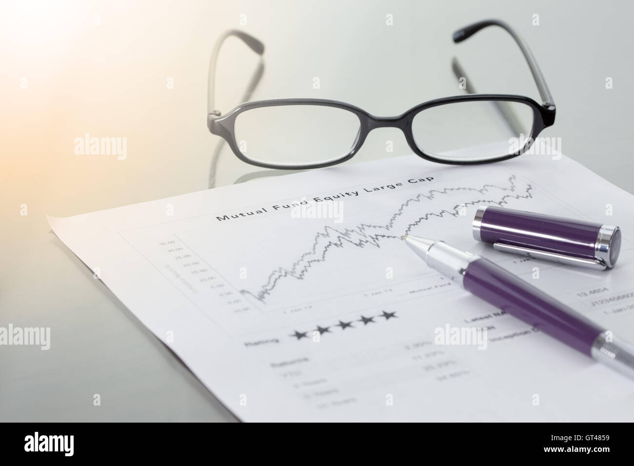 Mutual Fund information with performance line graph and benchmark with pen and glasses. - Stock Image