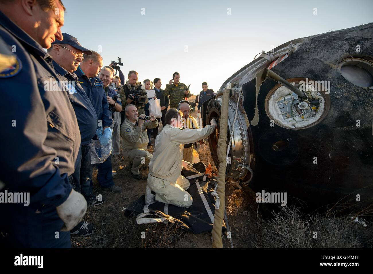 Russian support personnel work around the Soyuz TMA-20M spacecraft just minutes after landing with International Stock Photo