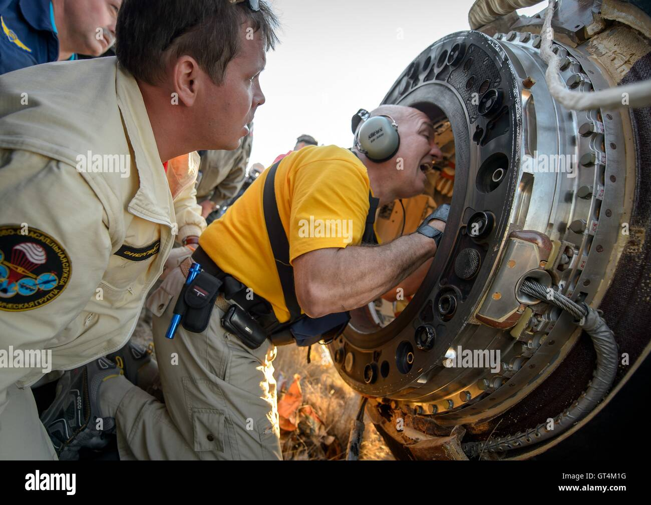 Russian support personnel work around the Soyuz TMA-20M spacecraft just minutes after landing with International - Stock Image