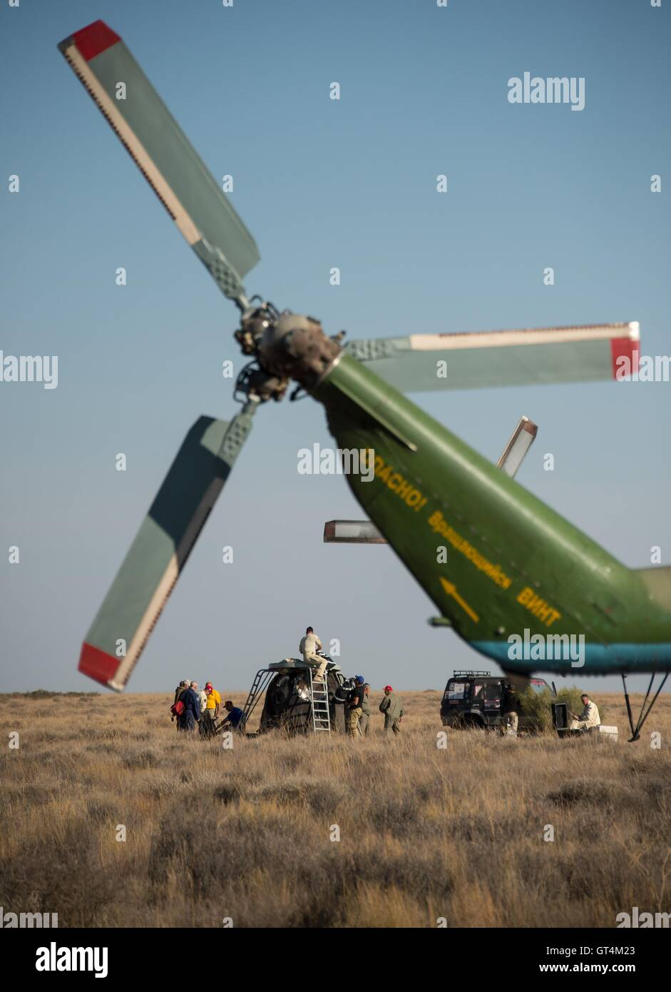 Russian support personnel work around the Soyuz TMA-20M spacecraft after landing with International Space Station - Stock Image