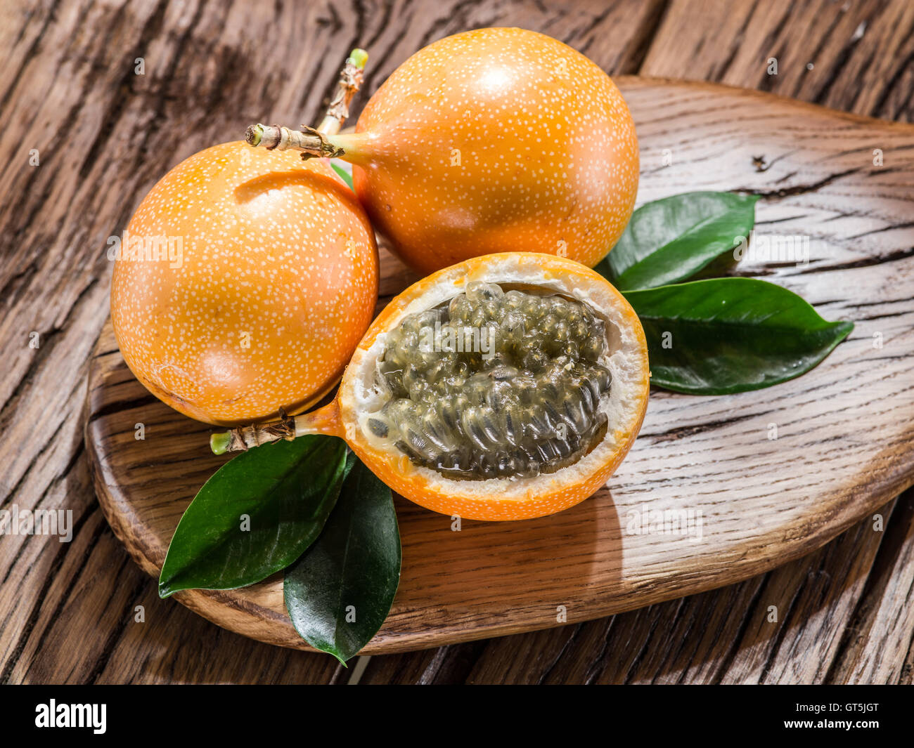 Granadilla fruits on the wooden table. - Stock Image
