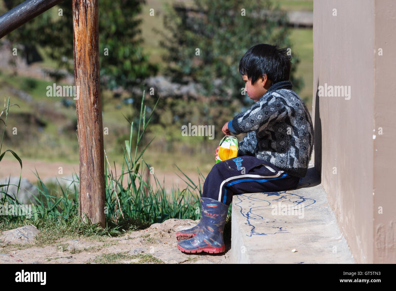 Chinchero Peru -May 18 : Young Andean boy with a large carton of fruit juice. May 18 2016, Chinchero Peru. - Stock Image