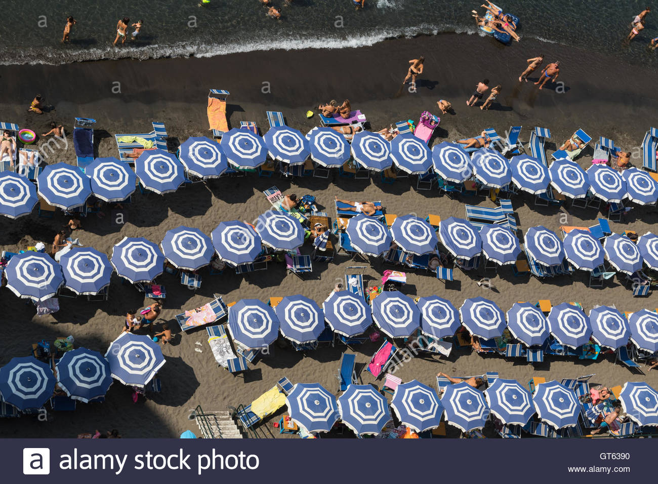 Overhead view of blue and white striped sunshades on a beach in Sorrento, Italy. - Stock Image