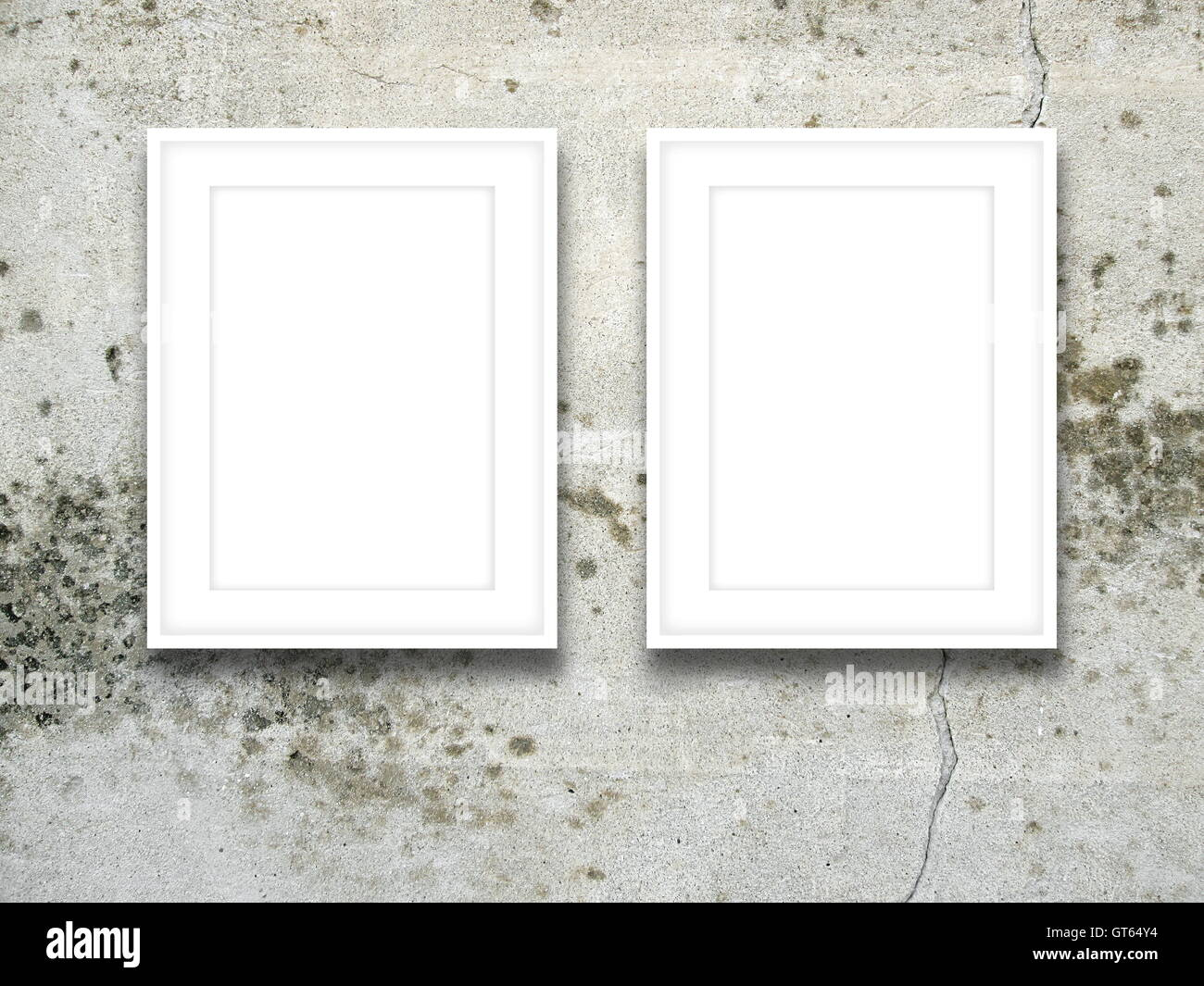 Close-up of two blank picture frames on gray cracked concrete wall background - Stock Image