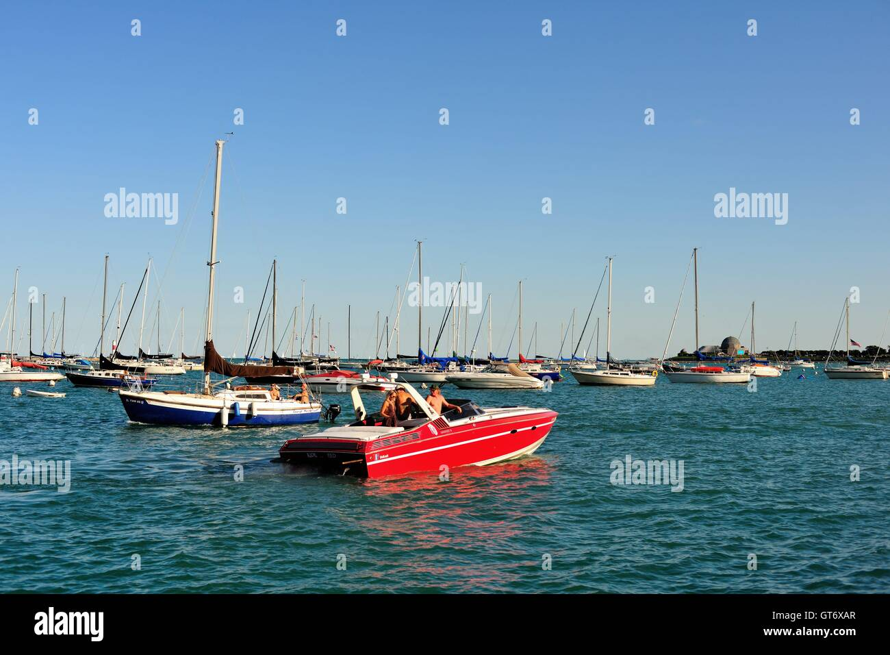 An outbound speed boat passes an incoming sailboat in Chicago's Monroe Street Harbor on Lake Michigan. Chicago, - Stock Image