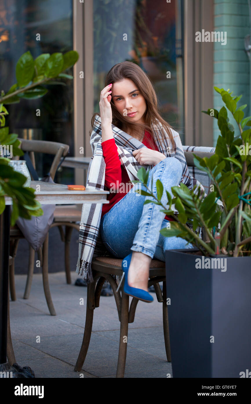 Young beautiful brunette girl sits in summer cafe in the street wrapped blanket Stock Photo